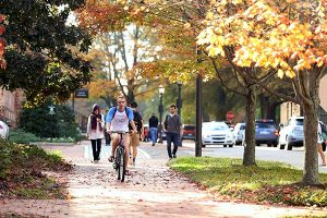 UNC student riding his bike down a brick sidewalk on UNC-Chapel Hill campus